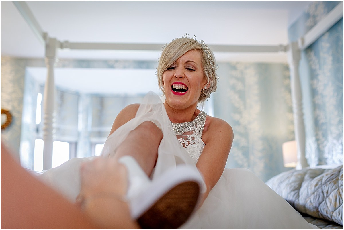 Southdowns Manor Wedding Photography puts on converse wedding trainers