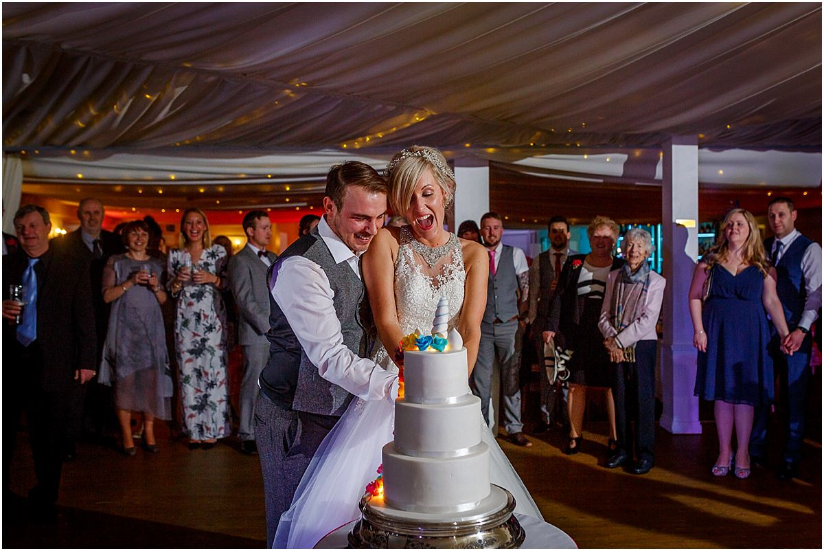 Southdowns Manor Wedding Photography bride and groom cut the wedding cake