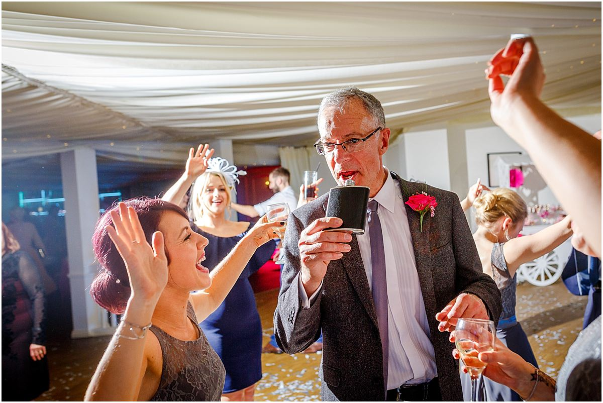 Southdowns Manor Wedding Photography father of the bride drinking from a hipflask