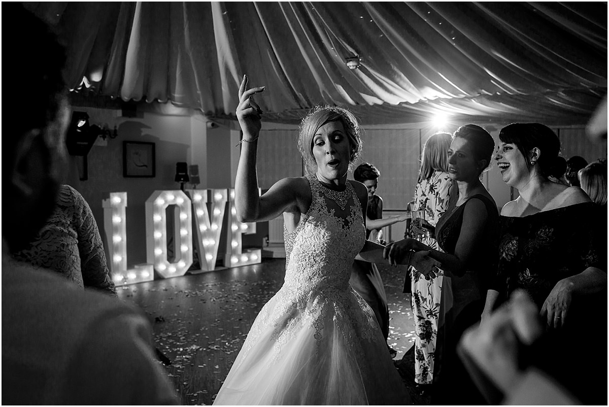 Southdowns Manor Wedding Photography sister of the bride dancing and laughing with hands up