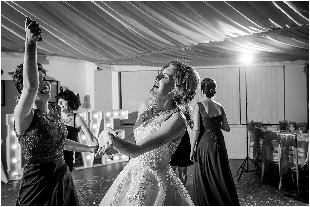 Southdowns Manor Wedding Photography sister of the bride and brides sister dancing and laughing