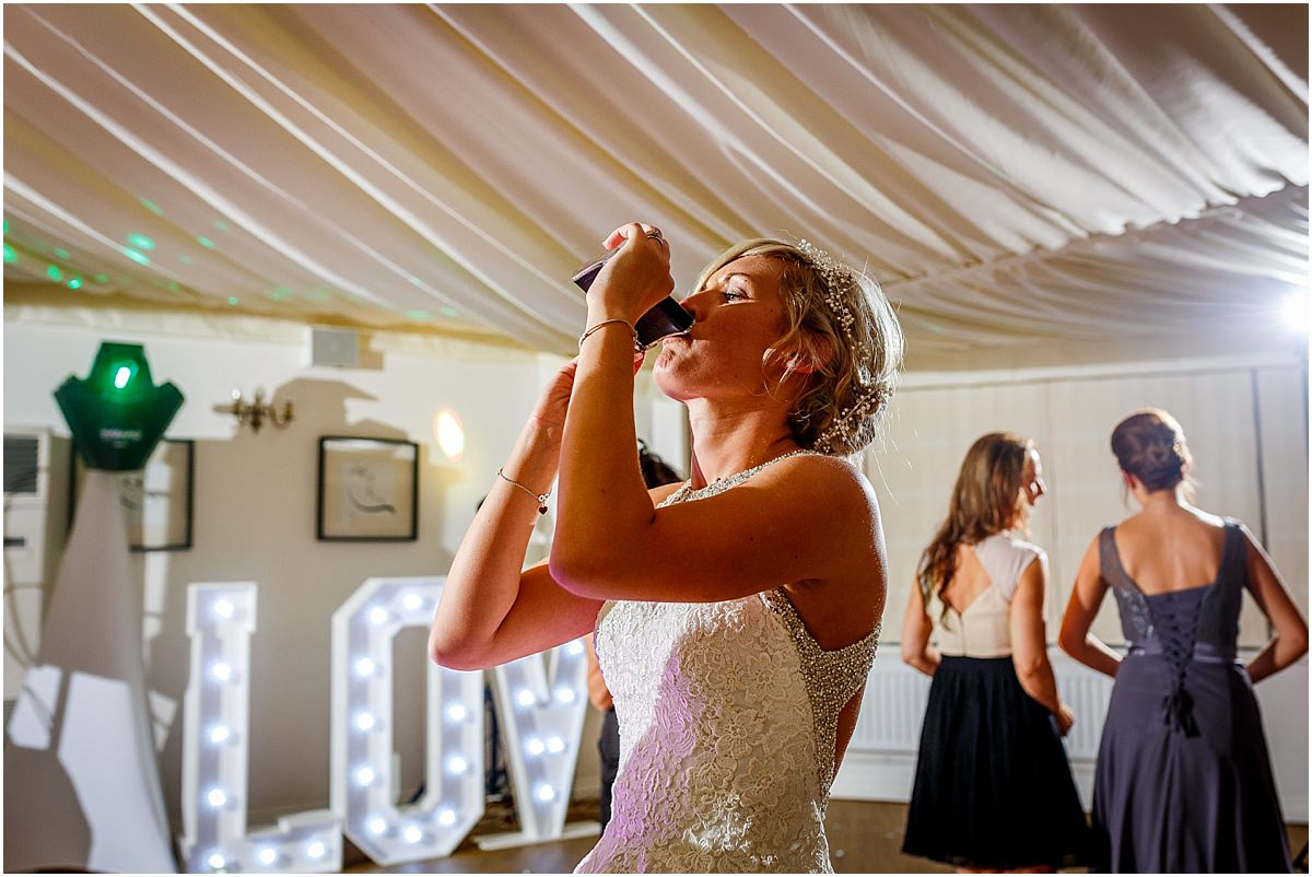 Southdowns Manor Wedding Photography bride drinking from a hipflask